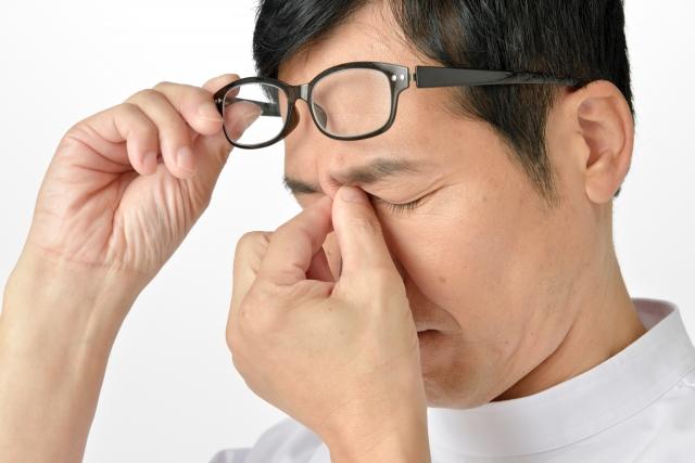 メガネで目が疲れて眉間を押さえてる