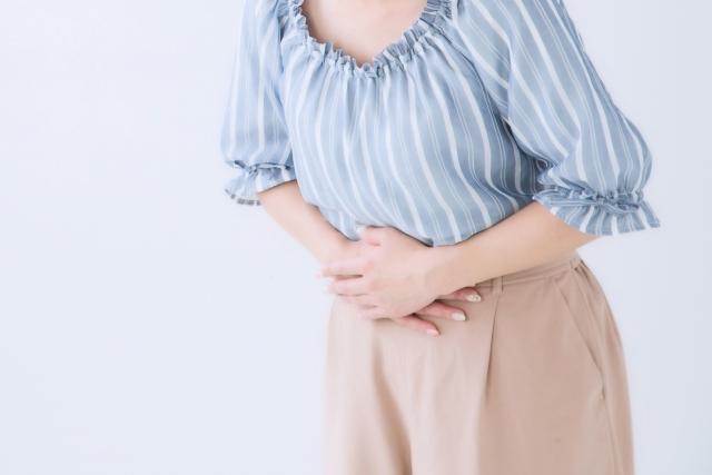 女性が腹痛でお腹を押さえている