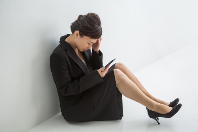 座りながらスマホを操作してる女性