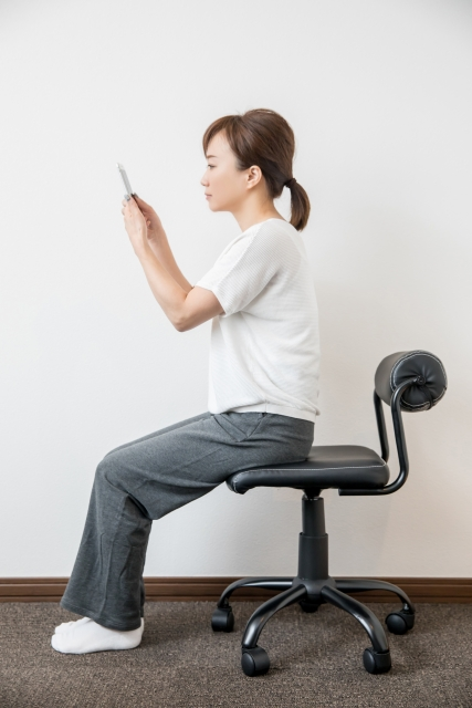 姿勢よく椅子に座って形態を触っている女性